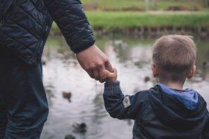 padre e figlio al lago per mano